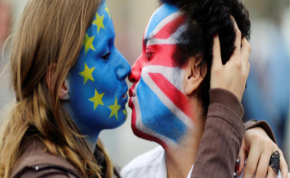 Two activists with the EU flag and Union Jack painted on their faces kiss each other in front of Brandenburg Gate to protest against the British exit from the European Union, in Berlin, Germany, June 19, 2016. REUTERS/Hannibal Hanschke