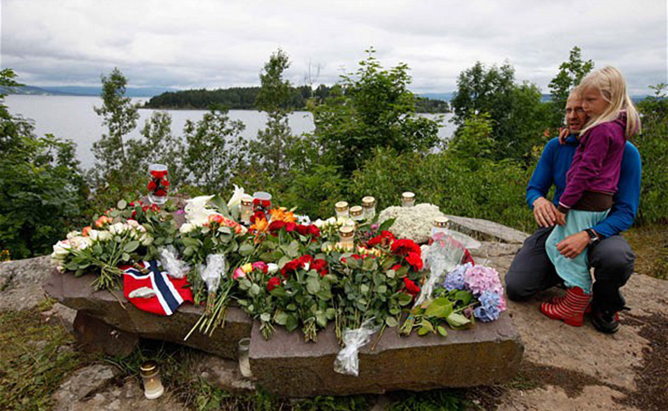 People mourn next to flowers in front of Utoeya island northwest of Oslo...People mourn next to flowers in front of Utoeya island, northwest of Oslo July 25, 2011. At least 93 people are dead after a gunman dressed in police uniform opened fire at a youth camp of Norway's ruling political party on Friday in Utoeya island, hours after a bomb blast in the government district in the capital Oslo. According to local media, four or five participants at the youth camp are still unaccounted for.   REUTERS/Fabrizio Bensch (NORWAY - Tags: CIVIL UNREST CRIME LAW)