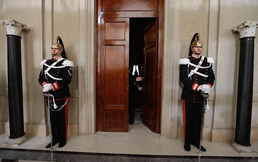 Corazzieri presidential honor guard officers patrol the entrance of the studio where Italian President Giorgio Napolitano meets party representatives at Rome's Quirinale presidential palace Saturday Dec. 22, 2012. Italy's President Napolitano is meeting with political leaders to set the stage for general elections early next year as Premier Mario Monti weighs whether to run for office after having handed in his resignation. Monti, appointed 13 months ago to steer Italy away from a Greek-style debt crisis, stepped down Friday after ex-Premier Silvio Berlusconi's party yanked its support for his technical government. (AP Photo/Alessandra Tarantino)